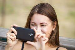 Muchacha feliz que toma la foto con su teléfono móvil Fotos de archivo