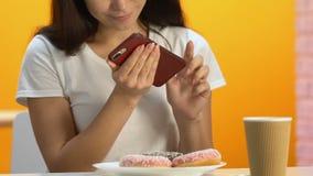 Muchacha feliz que toma la foto de buñuelos apetitosos en el teléfono móvil, alta comida de la caloría almacen de metraje de vídeo