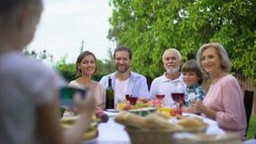 Muchacha feliz que toma la foto de familia con el smartphone, cena de la celebración, memorias metrajes