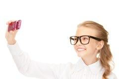 Muchacha feliz que toma la imagen con el teléfono celular Imágenes de archivo libres de regalías