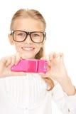 Muchacha feliz que toma la imagen con el teléfono celular Imagen de archivo