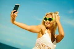 Muchacha feliz que toma la imagen del uno mismo con smartphone Imagenes de archivo