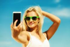 Muchacha feliz que toma la imagen del uno mismo con smartphone Foto de archivo libre de regalías