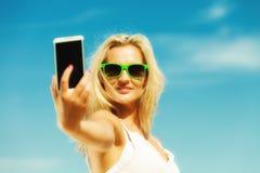 Muchacha feliz que toma la imagen del uno mismo con smartphone Imagen de archivo libre de regalías