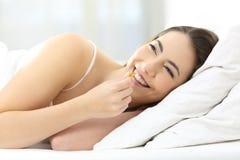 Muchacha feliz que toma la píldora en una cama en casa Imagen de archivo libre de regalías