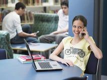 Muchacha feliz que usa el teléfono móvil en biblioteca Foto de archivo