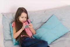 Muchacha feliz que usa el teléfono móvil mientras que se sienta en el sofá en casa Fotos de archivo libres de regalías