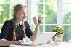 Muchacha feliz que usa la computadora portátil Imagen de archivo libre de regalías