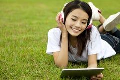 Muchacha feliz que usa la PC de la tablilla Foto de archivo libre de regalías