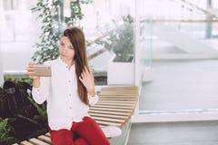 Muchacha feliz que usa un teléfono elegante en un caffe de la ciudad que se sienta en un banco Foto de archivo