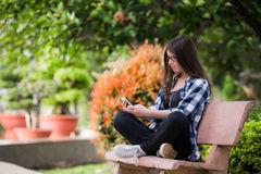 Muchacha feliz que usa un teléfono elegante en el parque de la ciudad que se sienta en banco Foto de archivo