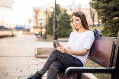 Muchacha feliz que usa un teléfono elegante en una ciudad que se sienta en un banco Imagen de archivo libre de regalías