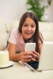 Muchacha feliz que usa un teléfono móvil Imágenes de archivo libres de regalías