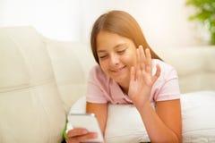 Muchacha feliz que usa un teléfono móvil que miente en la cama Fotos de archivo libres de regalías