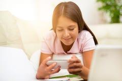 Muchacha feliz que usa un teléfono móvil que miente en la cama Fotografía de archivo libre de regalías