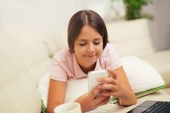 Muchacha feliz que usa un teléfono móvil que miente en la cama Foto de archivo