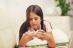 Muchacha feliz que usa un teléfono móvil que miente en la cama Fotos de archivo