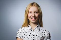Muchacha feliz Retrato del primer de adolescente hermoso en la camisa sport que sonríe mientras que se opone a fondo gris Imagen de archivo