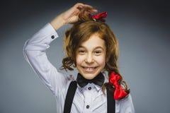 Muchacha feliz Retrato del primer de adolescente hermoso en la camisa sport que sonríe mientras que se opone a fondo gris Imagenes de archivo