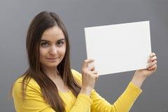 Muchacha feliz 20s relajada en la fabricación de un anuncio en la exhibición de un parte movible en blanco Fotos de archivo libres de regalías