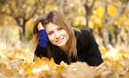 Muchacha feliz sonriente en parque del otoño Foto de archivo