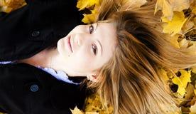 Muchacha feliz sonriente en parque del otoño Imagen de archivo