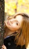 Muchacha feliz sonriente en parque del otoño Imagenes de archivo