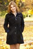 Muchacha feliz sonriente en parque del otoño Imágenes de archivo libres de regalías