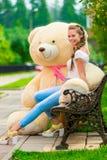 Muchacha feliz sonriente en un banco con su oso de peluche preferido en t Imagen de archivo libre de regalías