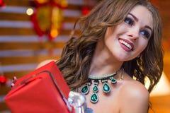 Muchacha feliz sonriente hermosa con un collar verde en su cuello que sostiene una caja de regalo roja en un fondo festivo del `  Fotos de archivo libres de regalías