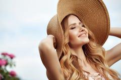 Muchacha feliz sonriente hermosa en vestido del vintage y sombrero de paja rosados foto de archivo