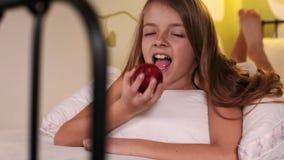 Muchacha feliz sonriente que come una manzana en cama almacen de video