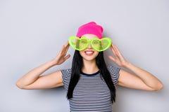 Muchacha feliz y divertida joven en camiseta rayada, sombrero y grande rosados Foto de archivo
