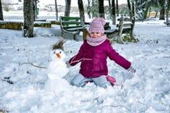 Muchacha feliz y el muñeco de nieve Fotografía de archivo