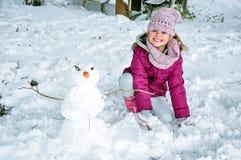 Muchacha feliz y el muñeco de nieve Foto de archivo libre de regalías