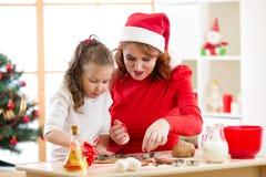 Muchacha feliz y madre del niño que cuecen las galletas de Navidad juntas en el sitio adornado festivo Fotografía de archivo
