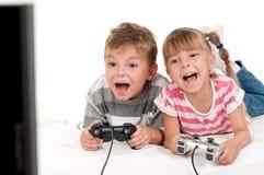 Muchacha feliz y muchacho que juegan a un juego video imagen de archivo