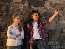 Muchacha feliz y muchacho sonrientes que toman selfies con smartphone Fotografía de archivo libre de regalías