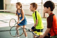 Muchacha feliz y muchachos que juegan a tenis Imagen de archivo