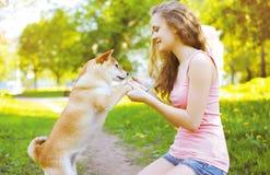 Muchacha feliz y perro que juegan en parque soleado del verano Imagenes de archivo