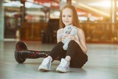 Muchacha feliz y sonriente con la mini muñeca segway y de la felpa del oso en t Fotografía de archivo