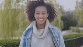 Muchacha feliz y sonriente de la raza mixta con corte de pelo afro que camina en el parque almacen de metraje de vídeo