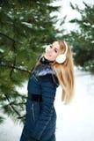 Muchacha feliz y sonriente del invierno al aire libre en madera de pino nevosa Foto de archivo