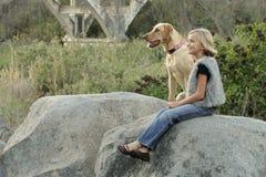 Muchacha feliz y su perro Foto de archivo