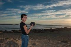 Muchacha femenina en la escena en la playa en la puesta del sol Foto de archivo