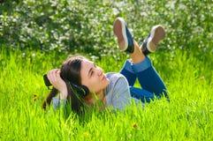 Muchacha femenina joven hermosa que escucha la música en el teléfono del jugador Imágenes de archivo libres de regalías