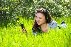 Muchacha femenina joven hermosa que escucha la música en el teléfono del jugador Foto de archivo