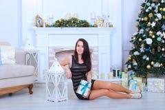 Muchacha femenina joven que se sienta en el piso, sosteniendo el regalo con ribbo azul Foto de archivo libre de regalías