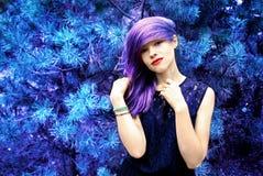 Muchacha festiva hermosa con el pelo azul en un fondo del árbol de hadas azul Imagenes de archivo