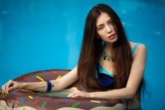 Muchacha flaca en un bañador azul que se coloca en una piscina imagen de archivo libre de regalías